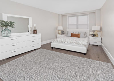Open master bedroom with hardwood floors and large window staged with white furniture and grey rug