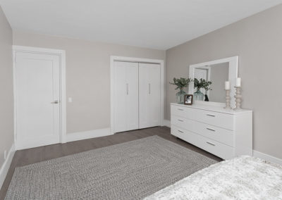Large master bedroom in apartment with hardwood floors and white furniture