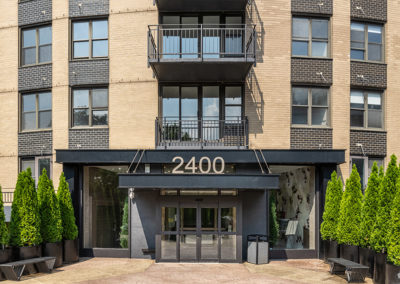 The exterior entrance of 2400 Hudson Apartments in Fort Lee, NJ, a tall, modern building with balconies