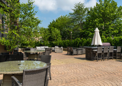 An outdoor cobblestone courtyard with tables, chairs, and shade umbrellas at 2400 Hudson Apartments