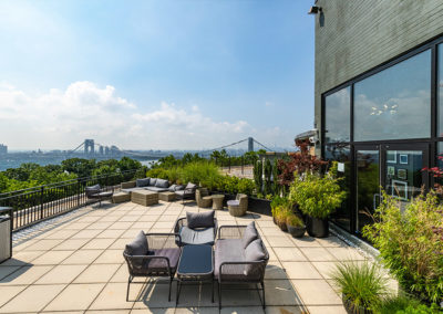 An apartment rooftop garden with tables, chairs, and lots of greenery and a view of the George Washington Bridge