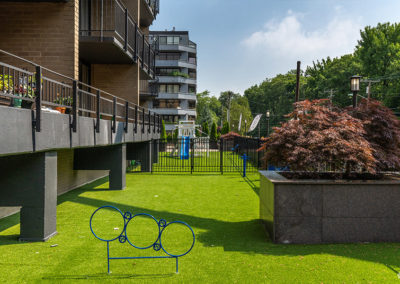 An outdoor area with grass outside of balconies at 2400 Hudson Apartments