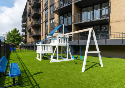 A children's playground on a patch of grass outside of 2400 Hudson Apartments in Fort Lee, NJ