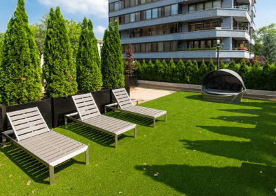 A rooftop lounging area with lounge chairs on a patch of green with shrubbery at apartment rental