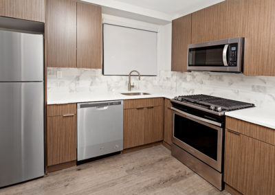 Wood grain kitchen cabinets with stainless steel appliances and backsplash at 2400 Hudson Apartments