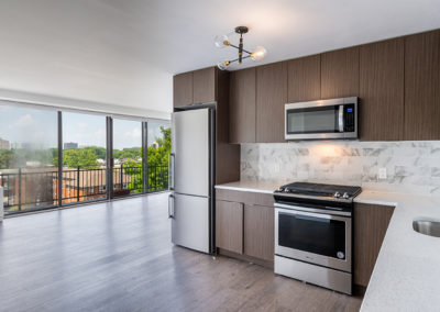 Luxury kitchen with dark wood cabinets, stainless steel appliances, and modern lighting in apartment for rent in Fort Lee, NJ
