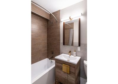Modern apartment bathroom with tub, rainfall shower, and vanity